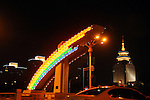 main road through Beijing at night, with neon rainbow lights and lighted buildings