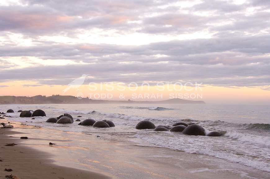 Group of Moeraki Boulders at sunrise Pink clouds | headland in background | rocks in silhouette | Coastal Otago New Zealand
