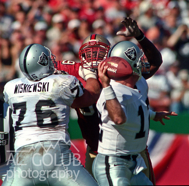 San Francisco 49ers vs. Oakland Raiders at Candlestick Park Sunday, October 8, 2000.  Raiders beat 49ers in OT 34-28.  Oakland Raiders guard Steve Wisniewski (76) holds off San Francisco 49ers defensive tackle Brentson Buckner (99) as quarterback Rich Gannon (12) pass ball.