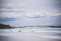 Surfer surfing at Rarawa Beach, a popular and beautiful white sand beach in Northland Region, North Island, New Zealand
