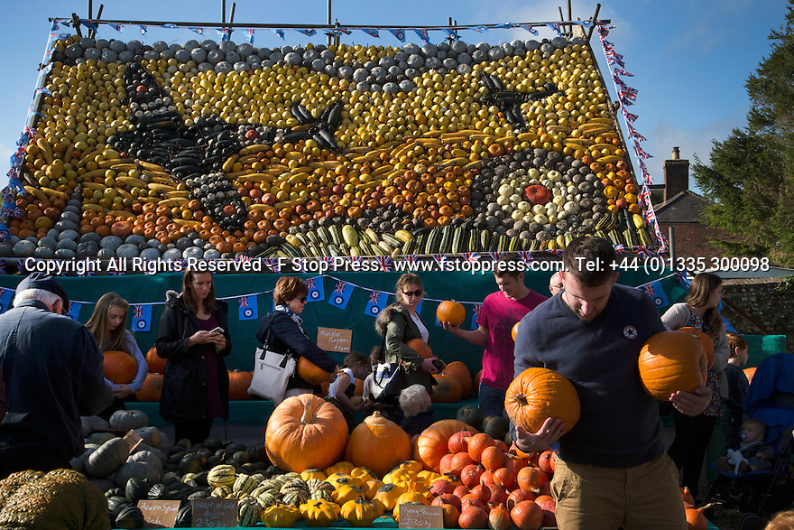 27/10/14<br /> <br /> Families enjoying the half term sunshine flock to buy their pumpkins for Halloween from a cottage-garden in Slindon, near Chichester West Sussex. This year a backdrop made entirely from pumpkins and squashes depicts a scene from the Battle of Britain marking 75 years since the Spitfire came into service. It shows two Spitfires in D Day colours (white stripes on the wings) flying over the spire of Chichester Cathedral and also an RAF roundel.<br /> <br /> All Rights Reserved - F Stop Press.  www.fstoppress.com. Tel: +44 (0)1335 300098