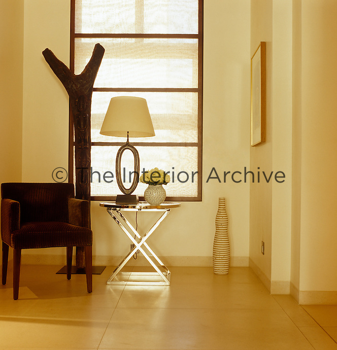 An ethnic wooden sculpture, armchair and chrome side table are grouped in front of the window