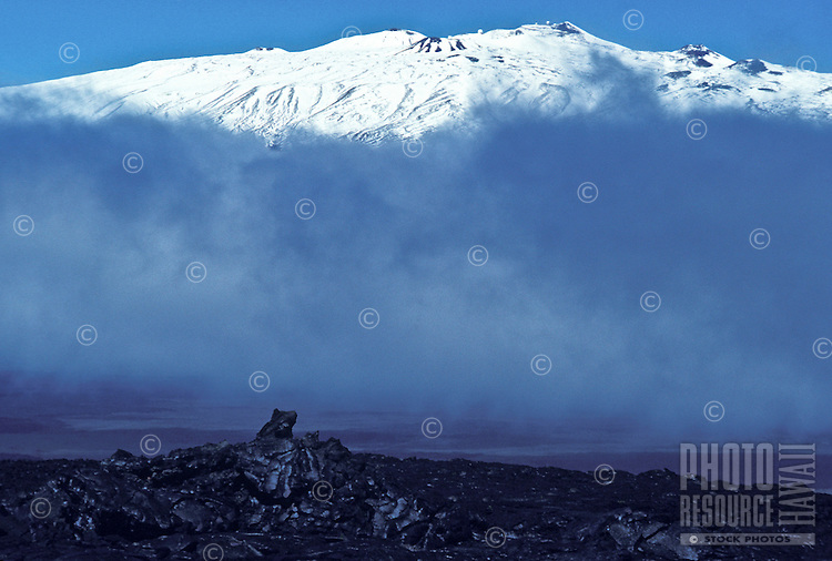 Snowcapped Mauna Kea, 14,000 in elevation, with hardened black pahoehoe lava in foreground