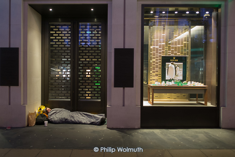 Rough sleeper in the doorway of a luxury store, Oxford Street, London.