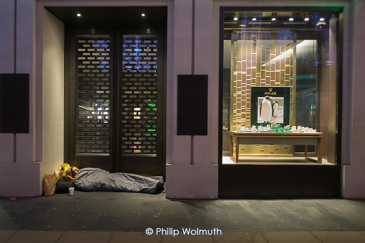 Rough sleeper in the doorway of a luxury store, Oxford Street, London.