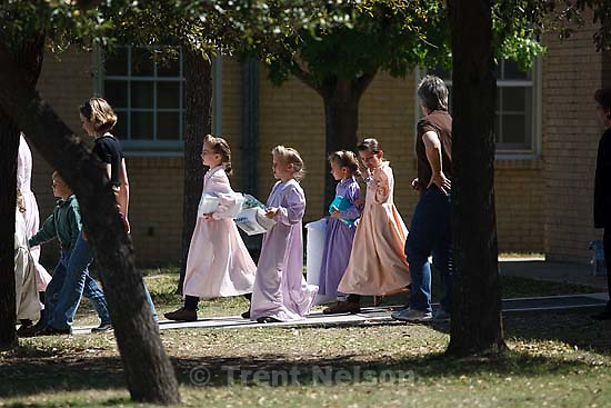 Eldorado - FLDS women and children from the YFZ Ranch are escorted by Texas Child Protective Services workers from the First Baptist Church's Fellowship Hall to waiting buses Sunday, April 6, 2008.