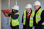© Joel Goodman - 07973 332324 .  04/02/2014 . Manchester , UK . L-R apprentice joiner with a nail gun , Mike Kane and Ed Balls . Ed Balls , MP for Morley and Outwood and Shadow Chancellor of the Exchequer the Labour Party , joins Labour candidate Mike Kane on the campaign trail ahead of the Wythenshawe and Sale East by-election , following the death of MP Paul Goggins . They visit apprentices at the Leybrook Road building site in Wythenshawe where apprentice builders work on bungalows built for affordable rent . Photo credit : Joel Goodman