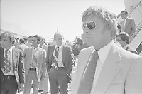 """Upon arriving at McClellan Air Force Base 7 miles northeast of Sacramento, California at 3:10 PM[1] on September 5, 1975 after the 10:04 am assassination attempt by Lynette """"Squeaky"""" Fromme on his life, President Ford waits to board Air Force One and return to Washington. Also shown are Secret Service agents, including Larry Buendorf in foreground with sunglasses, and Chief of Staff Don Rumsfeld (descending ramp of plane)."""