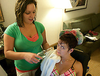 Karisa helps Kara with a beer during her birthday party in a Syracuse hotel room.