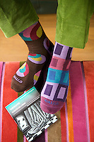 Two of Paolo Bagnara colourful sock designs seen against the striped velvet ottoman in the living room