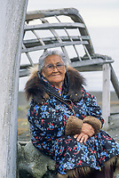 89 year old native Alaska woman, Bertha Leavitt in traditional Parka, leans against an Umiak (whaling boat) on the beach of Arctic Ocean, Utqiagvik (Barrow), Alaska. (taken in 2000)