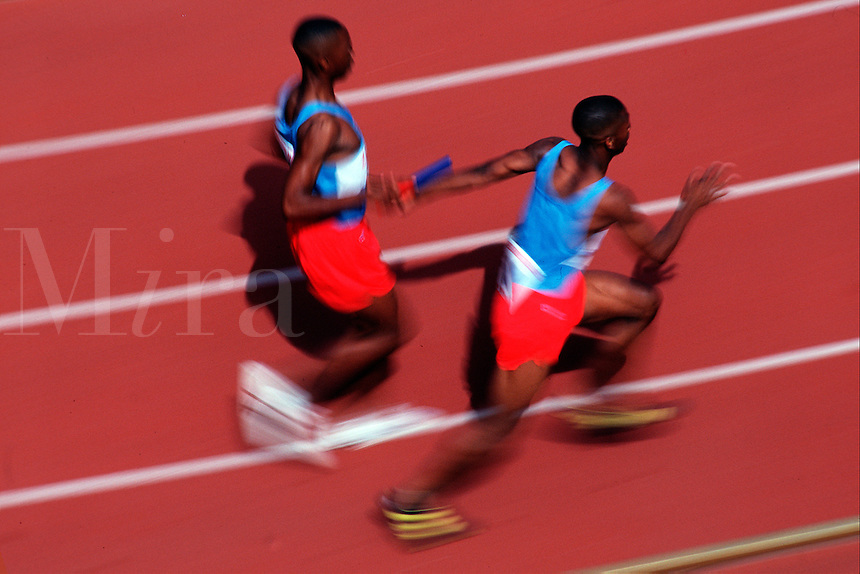 Male relay runners at a track meet hand off the baton.