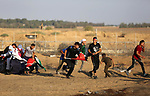 A wounded Palestinian protester is evacuated during clashes with Israeli troops following the tents protest where Palestinians demand the right to return to their homeland at the Israel-Gaza border, in Khan Younis in the southern Gaza Strip, on October 11, 2019. Photo by Ashraf Amra