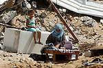 A Palestinian woman bakes bread on the firewood amid the rubble of her destroyed house in the town of Khan Younis in the southern Gaza Strip, Sep. 21, 2014. Gazans who endured more than 50 days of devastating Israeli bombardment are now eager to enjoy some life and many are rushing back to a veneer of normalcy. Photo by Abed Rahim Khatib