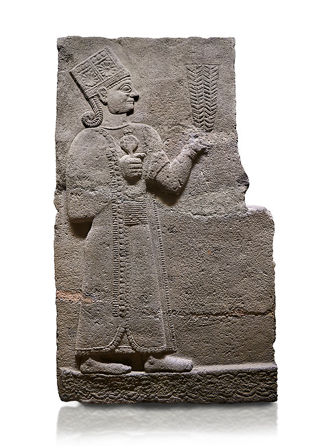 Hittite relief sculpted orthostat stone panel of Long Wall Basalt, Karkamıs, (Kargamıs), Carchemish (Karkemish), 900-700 B.C. Anatolian Civilisations Museum, Ankara, Turkey<br /> <br /> Goddess Kubaba. Goddess is depicted from the profile. She holds a pomegranate in her hands on her chest. She carries a one-horned headdress on her head. Her braided hair hangs down to her shoulder . <br /> <br /> On a White Background.
