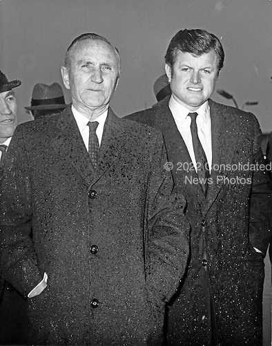 """Camp Springs, MD - (FILE) -- United States Senate Majority Leader Mike Mansfield (Democrat of Montana), left, and Senate Majority Whip Edward M. """"Ted"""" Kennedy, right, stand unprotected from the rain as they await the arrival of U.S. President Richard M. Nixon (not pictured), who was leaving for his first trip to Europe as President at Andrews Air Force Base in Camp Springs, Maryland on February 23, 1969..Credit: Arnie Sachs / CNP"""