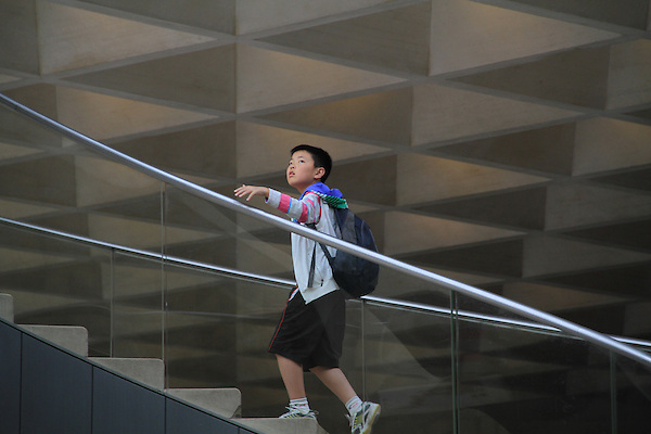 Asian boy on the stairway entry to the Louvre Museum in Paris, France. .  John offers private photo tours in Denver, Boulder and throughout Colorado, USA.  Year-round. .  John offers private photo tours in Denver, Boulder and throughout Colorado. Year-round.