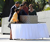 United States President Barack Obama, flanked by daughters Sasha (L) and Malia (R) examine a time capsule along with first lady Michelle Obama (2nd,R) and Michelle's mother Marian Robinson as they arrive for the dedication of the Martin Luther King, Jr Memorial on the National Mall in Washington DC USA, October 16, 2011.  The ceremony for the slain civil rights leader had been postponed earlier in the summer because of Tropical Storm Irene.  .Credit: Mike Theiler / Pool via CNP