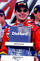 NASCAR driver Jeff Gordon holds his trophy in Victory Lane after winning the Diehard 500 at Talladega, AL  Sunday, 4/16/00. (Photo by Brian Cleary)