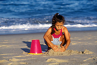 Girl playing in the sand at the beach, Cape Cod