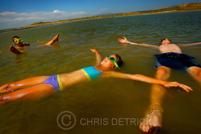 The Troger children Lena, 9, center, Tobias, 11, right, and Jonathan, 7, take advantage of the buoyancy of the Great Salt Lake and float off the shore of Antelope Island.  The Lake is endorheic and therefore has very high salinity, much saltier than the ocean.<br />