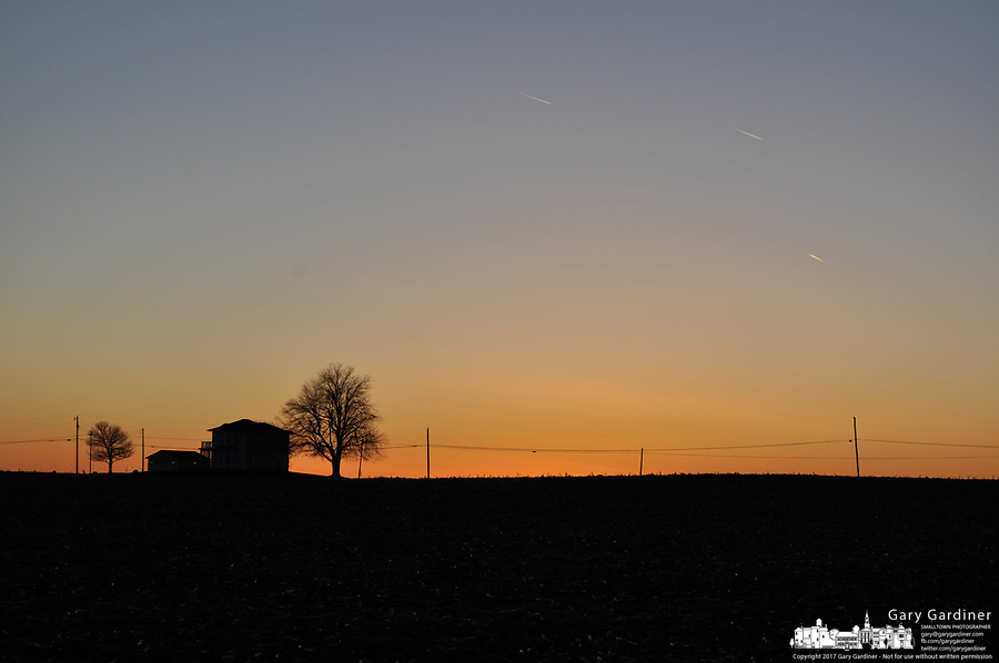 Farm house silhouetted against sunset on a cold winter day.