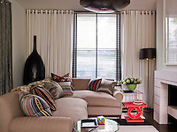 The sofa is piled with a collection of brightly coloured cushions
