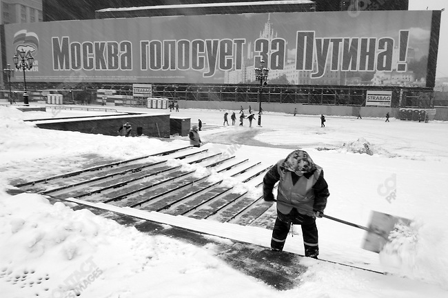 """As a worker cleared up the first heavy snow of winter in Moscow a banner of the United Russia party next to then Kremlin on Manezh Square proclaimed, """"Moscow is voting for Putin."""" November 15, 2007"""