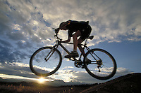 Woman mountain biking at sunset in the Rocky Mountains of Colorado. Ellie Pryor (MR 617). Colorado.