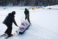 Checkpoint volunteers move musher's food bags from the plane to the Eagle Island checkpoint on Saturday afternoon.  Eagle Island is a remote tent checkpoint which has a ton of snow this year.  Iditarod 2009