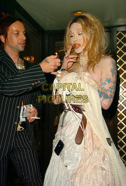 PETE BURNS & PARTNER.At the Miss Great Britain Awards,.Grosvenor House Hotel, London, .25th February 2006..half length wig tattoo tattooes lighting up a cigarette cigar smoking .Ref: CAN.www.capitalpictures.com.sales@capitalpictures.com.©Capital Pictures