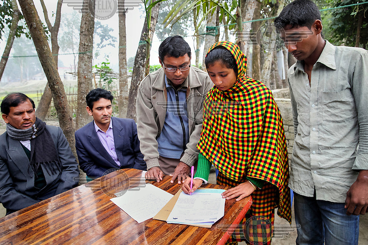 Arjina Begum (25) signs the agreement that she has made at the Shalish, a social system for informal adjudication of petty disputes. She had made a complaint of domestic violence against her husband Iliash Miah (27).