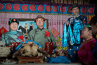A Mongolian bride (R) and parents perform a traditional rite during a wedding ceremony in Damao Banner, Inner Mongolia, China, October 2014.