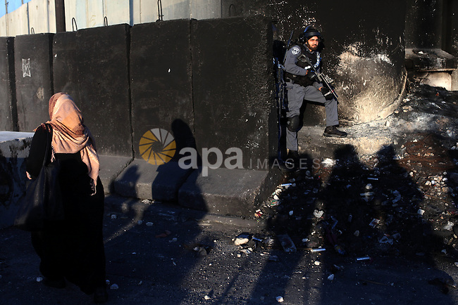 A Palestinian woman walks past an Israeli security officer as she makes her way through the Qalandia checkpoint between Ramallah and Jerusalem, in the occupied West Bank, to reach the al-Aqsa mosque compound in Jerusalem's Old City for traditional Friday prayers, the first of Islam's holy month of Ramadan on July 4, 2014. Israeli authority has forbidden access to Al-Aqsa mosque to muslim men under 50 years old and for muslim women under 40. Photo by Shadi Hatem