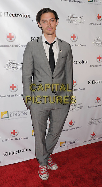 Tom Payne.Santa Monica Red Cross Chapter Annual Red Tie Gala Held at Fairmont Miramar Hotel, Santa Moinica, California, USA..April 21st, 2012.full length grey gray suit converse trainers sneakers shoes hands in pockets .CAP/ROT/TM.© TM/Roth/Capital Pictures