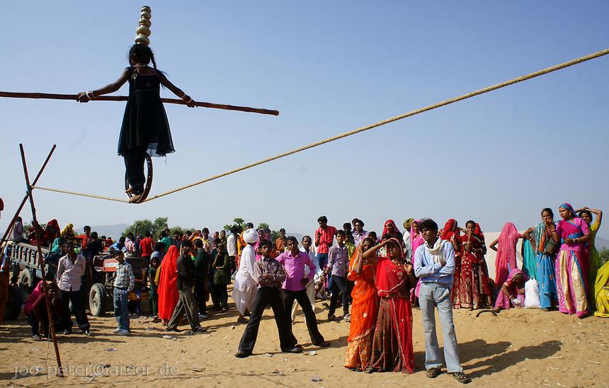 girl acrobat Aarti  showing her art at camel market in holy city Pushkar, Rajastan, India