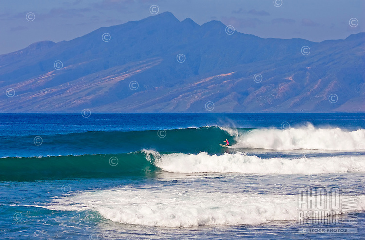 A lone surfer rides a clean wave at Honolua Bay, Maui, with the island of Molokai in the background.