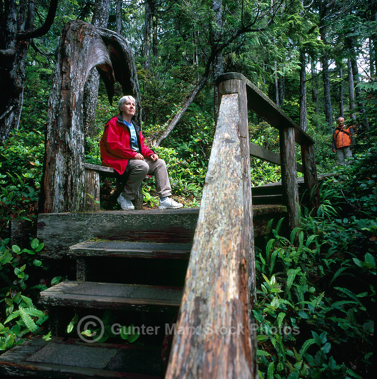 Hiker resting on Bench on Boardwalk Trail along Pacific West Coast of Vancouver Island, near Ucluelet, BC, British Columbia, Canada (Person in foreground is Model Released)