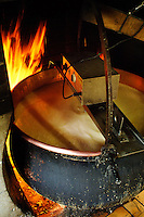 The milk (already partly separated into curds and whey) is heated up on the open wood fire in the copper cauldron to its top temperature while being stirred by a electrical mixer. ..Cowherd and cheesemaker spends 100 days in the summer, high up in the mountains, tending cows and pigs and making cheese at Balisalp and Käserstatt near Meiringen, Switzerland.