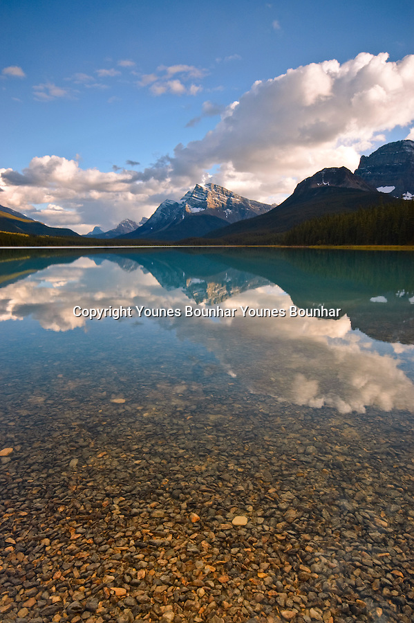 Moving clouds over waterfowl lake reflecting Mount Howse