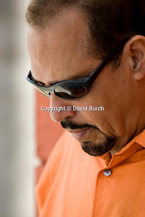 Mature hispanic man in sun glasses looking pensive
