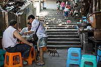 Lunch customers pay their bill at a dou hua restaurant near the top of Shibati, 18 steps, in the central Yuzhong District of Chongqing, China. Dou hua is a porridge-like dish made of very soft tofu. Shibati is an old neighborhood centered around this staircase. The area is slated for renovation and all businesses and residents must be gone by October 2014.