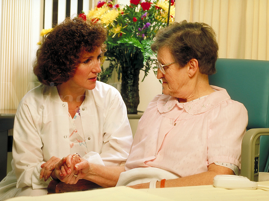 Nurse talks with elderly female patient in her hospital room.