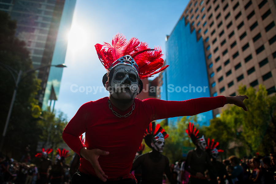 Mexican men, wearing feather headgears inspired by Aztecs, dance on the street during the Day of the Dead festival in Mexico City, Mexico, 29 October 2016. Day of the Dead (Día de Muertos), a syncretic religious holiday combining the death veneration rituals of the ancient Aztec culture with the Catholic practice, is celebrated throughout all Mexico. Based on the belief that the souls of the departed may come back to this world on that day, people gather at the gravesites in cemeteries praying, drinking and playing music, to joyfully remember friends or family members who have died and to support their souls on the spiritual journey.