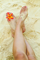Woman's legs in white sand with pink plumeria floewr between her toes