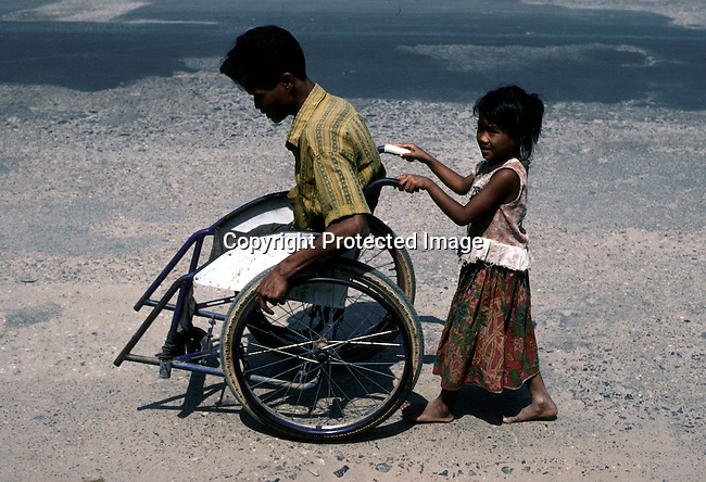 A girl is pushing a man's wheelchair on March 27, 1998 in central Phnom Penh, Cambodia. He lost his legs to a mine. Thousands of people have lost their limbs in the country due to the large amount of landmines in the rural areas all over the country.   .(Photo: Per-Anders Pettersson/ Liaison Agency)