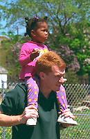 Man has girl on shoulders age 28 and 3. In the Heart of the Beast May Day Festival and Parade Minneapolis  Minnesota USA