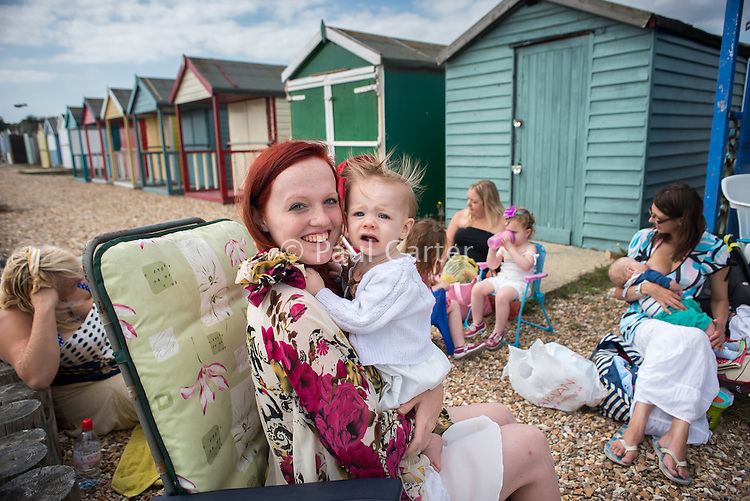 A mother and her baby look to camera with her friend breastfeeding in the background while sitting outside a beach hut.<br /> <br /> Image from the breastfeeding collection of the &quot;We Do It In Public&quot; documentary photography picture library project: <br />  www.breastfeedinginpublic.co.uk<br /> <br /> <br /> Hampshire, England, UK<br /> 03 /09/2013<br /> <br /> &copy; Paul Carter / wdiip.co.uk