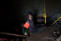 N. Uganda, Kitgum District. Peter C. Alderman Foundation project. David Olworo (37 yrs), had 3 brothers killed by rebels. He has HIV AIDS & suffers from depression. His feet are so swollen from this he elevates them from the ceiling. He can't walk & shifts from place to place on his buttocks. He relies on the help of neighbors & a remaining sister for food, water & his ART medication. He is suicidal but his Christian beliefs prevent him from killing himself and continue on with what he feels is a worthless life.