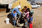 Palestinians fill plastic bottles and jerry cans with drinking water from a water tank in the West Bank village of Um Alkhair south of Hebron on August 17, 2016. Photo by Wisam Hashlamoun